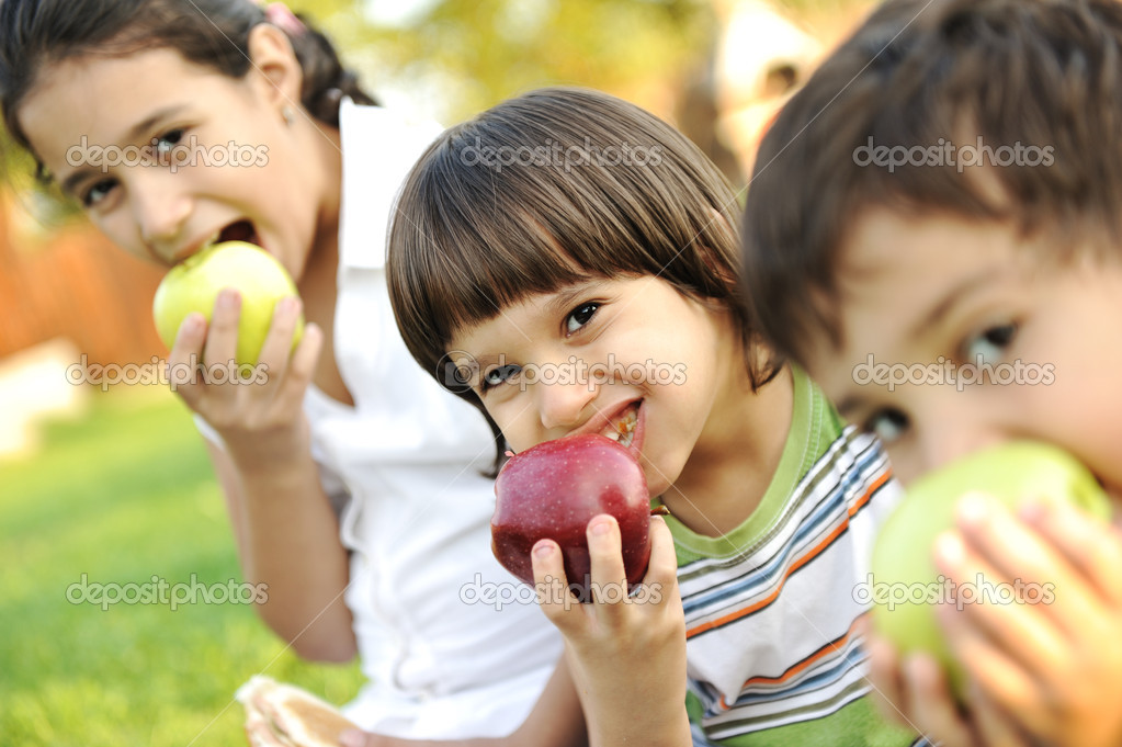 Small group of children eating apples together, shalow DOF