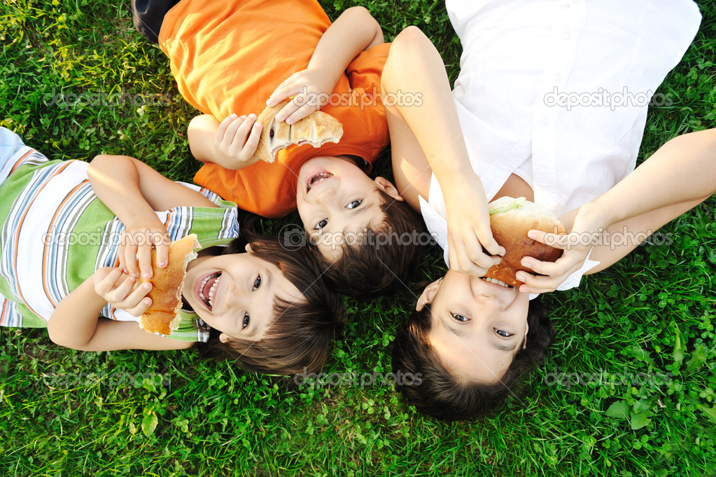 Three children laying on green grass on ground and eating sandwiches and sm