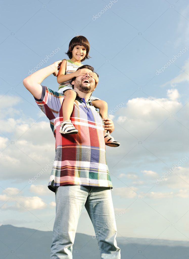 Young father and his son on back, piggyback, pikaboo playing, outdoor scene