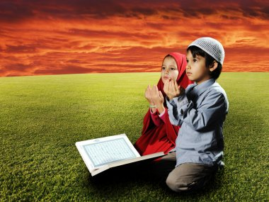Two Muslims children sitting on meadow in Ramadan and reading Koran and pra