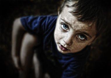 Sad looking child portrait on black background