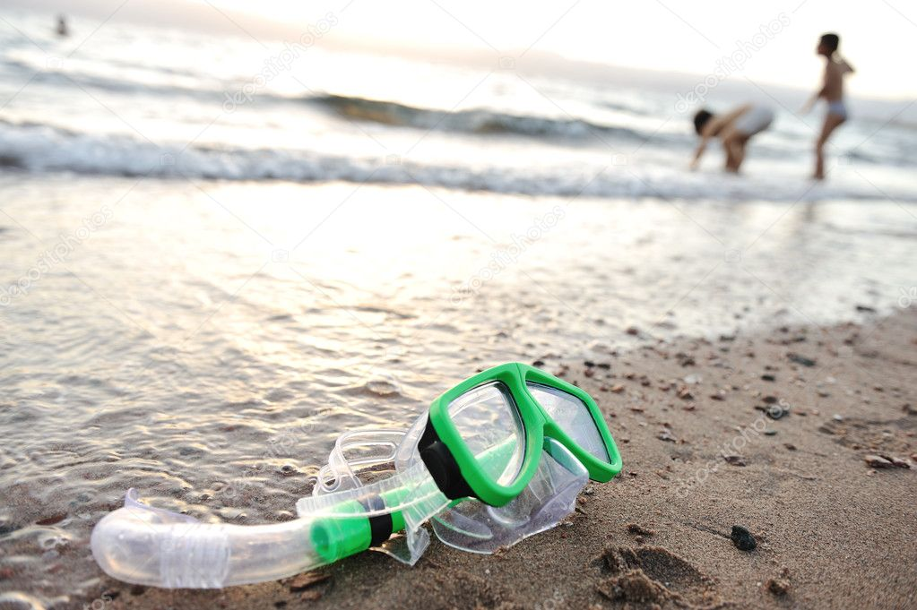 Snorkeling mask on the beach, children playing around