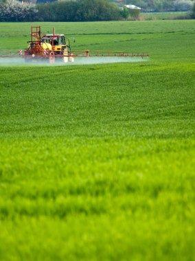 Tractor spraying on green farm