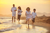 Fotografie Happy young family have fun on beach at sunset