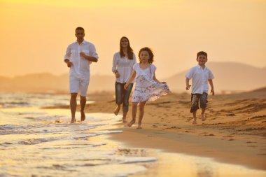 Счастливая молодая семья весело на пляже на закате