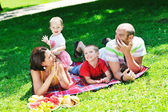 šťastný mladý pár s dětmi bavit v parku