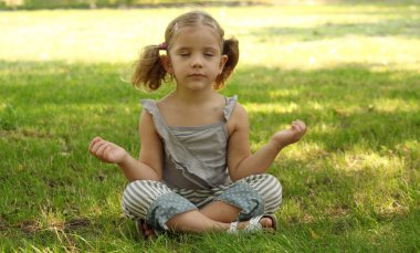 Little girl meditating in park
