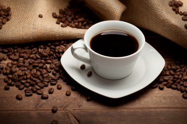 Cup of coffee and beans on jute background