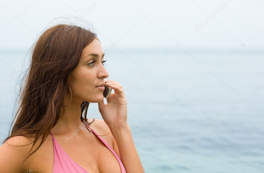 Attractive girl talking on a mobile on the beach.