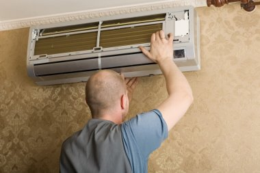 Technician installs a new air conditioner in the apartment