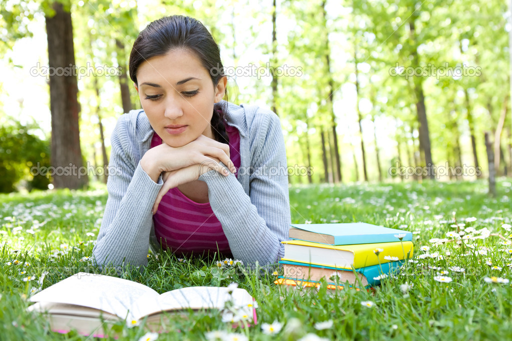 Woman on green field and reading