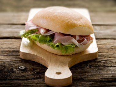 Sandwich with parma ham and green salad
