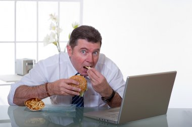 Manager eating unhealthy food at work place