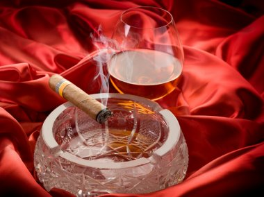 Cuban cigar and and glass liquor over red satin