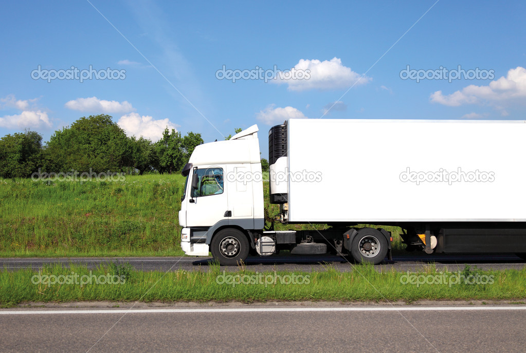 Long lorry with white truck and trailer on highway against blue sky.