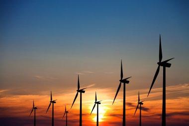 Wind turbines at sunset stock vector