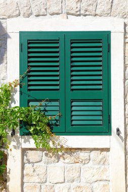 The window with wooden shutters of the old house