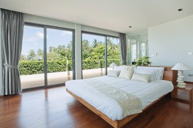 Panoramic view of nice cozy bedroom with tropical outdoor