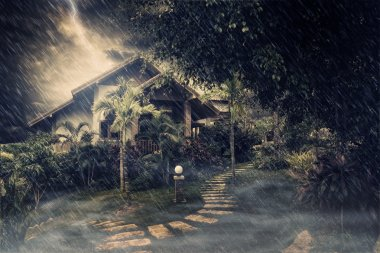 View of misty summer house during stormy night