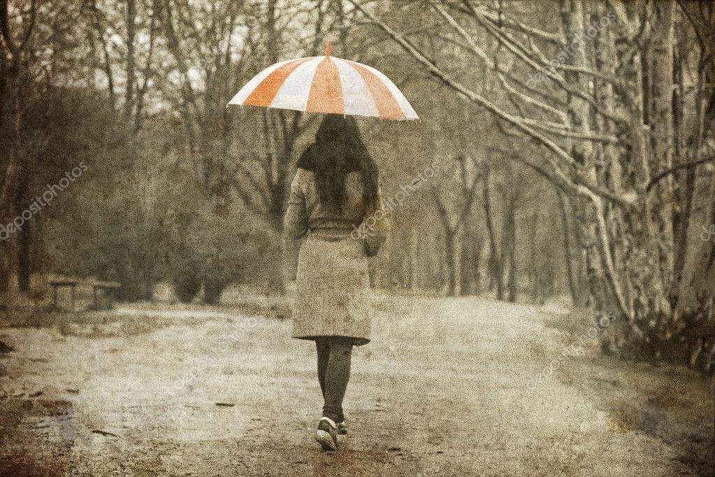Lonely girl walking at alley in the park in rainy day.