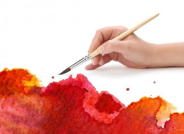 Hand with artist brush and abstract paint