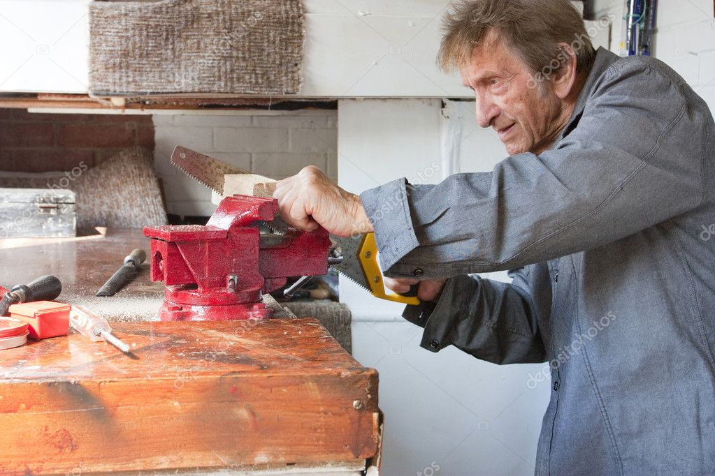 Old elderly man sawing in workshop shed