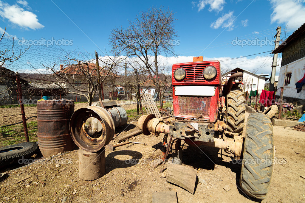 Beaten up old tractor in the countryside, on a jack