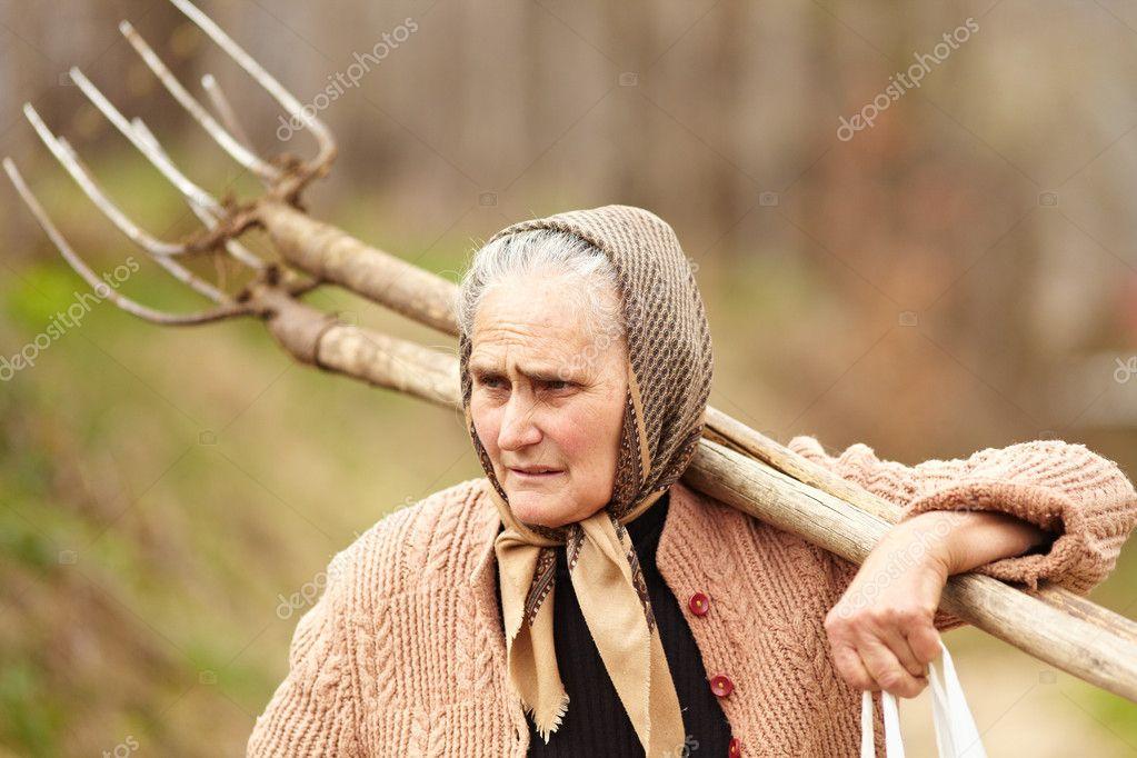 Senior farmer woman with a fork