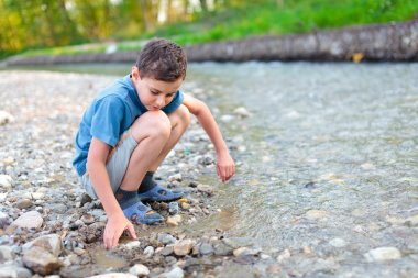 Child playing on a river bank