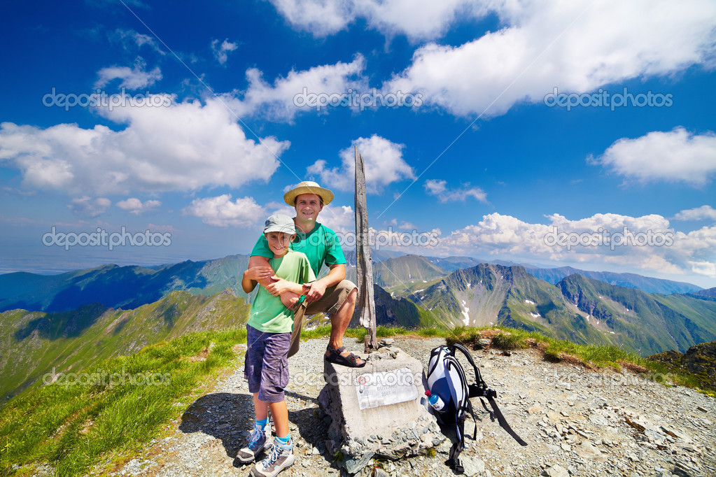 Father and son on Buteanu peak in Romanian mountains