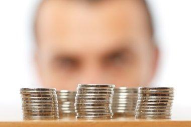 Businessman looking at piles of pennies
