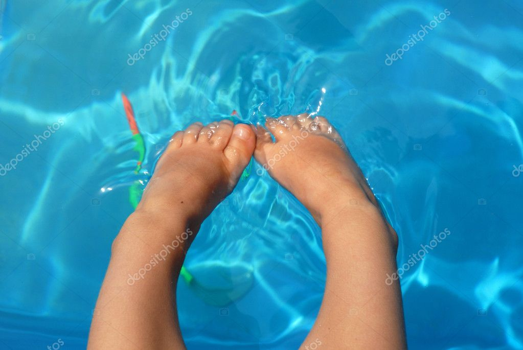 Legs of a child into the water