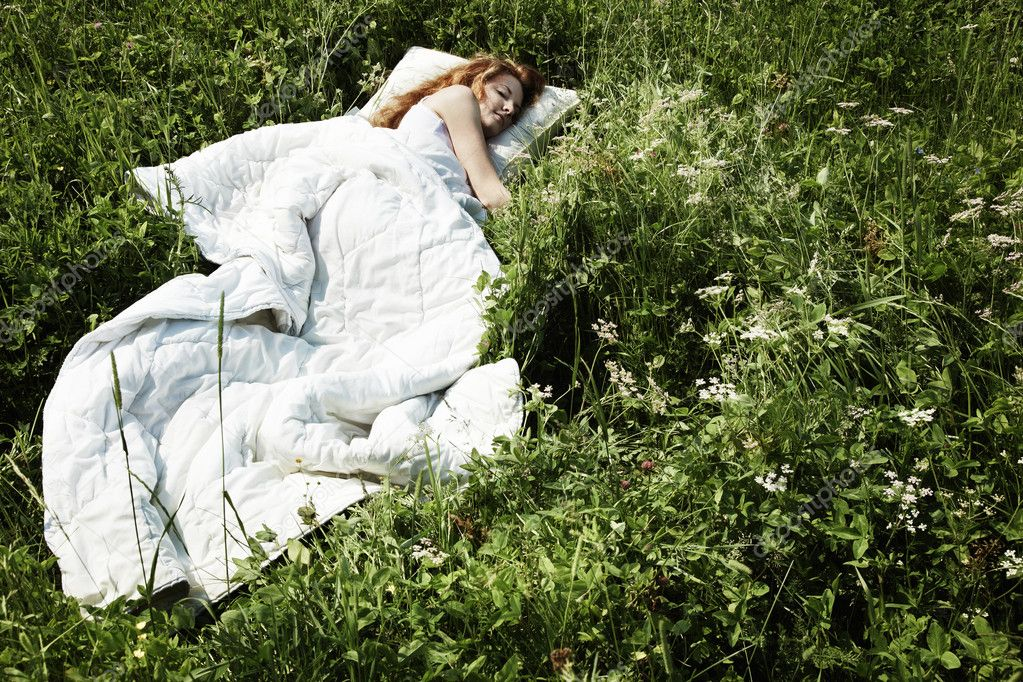 Portrait of the sleeping young woman on a meadow
