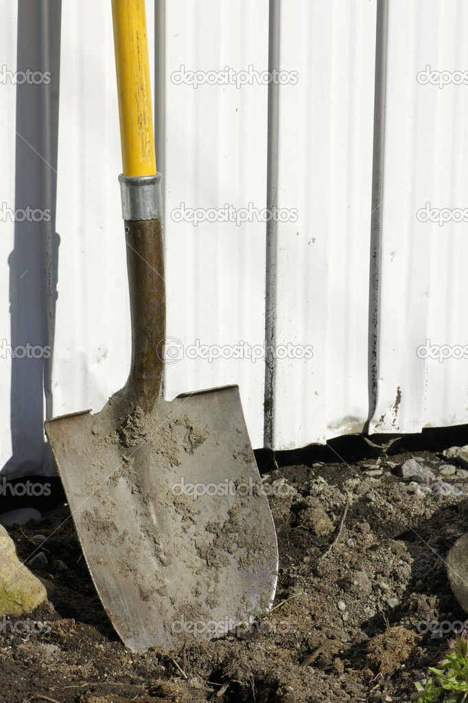 Shovel in earth against garden shed