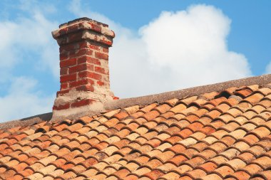 Tile roof with brick chimney against a blue sky stock vector