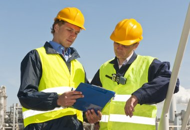 Two petrochemical engineers wearing safety vests and a hard top going over a checklist stock vector