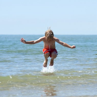 Boy jumps over wave