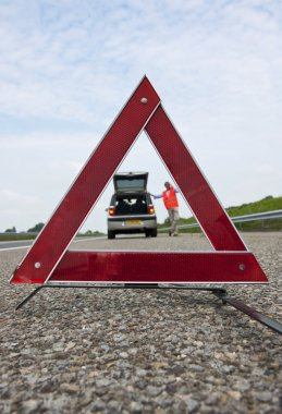 Warning triangle, with a broken down car and a man calling for assistance, out of focus in the backgrond stock vector
