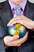 Businessman carrying world globe