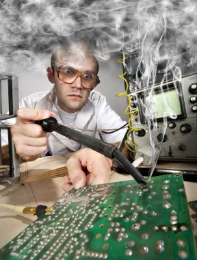 Funny nerd scientist soldering at vintage laboratory