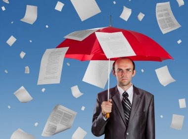 Serious businessman with red umbrella under falling documents stock vector