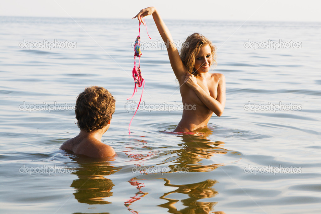 Sexy girl undressing in the water with boyfriend