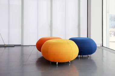 Three different color rounded sofas