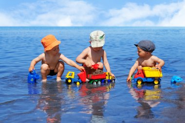 Three boys playing on the beach in the water