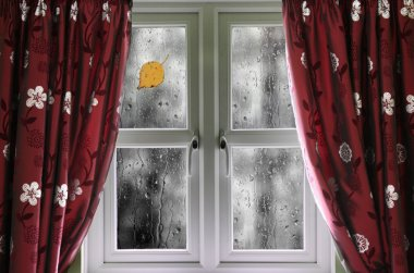 Rain on a window with curtains
