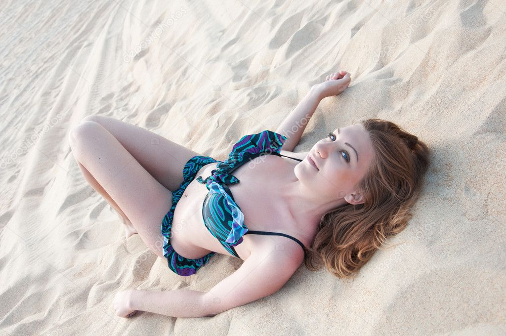 Beautiful Woman In A Bathing Suit Lying On The Sand Stock Photo