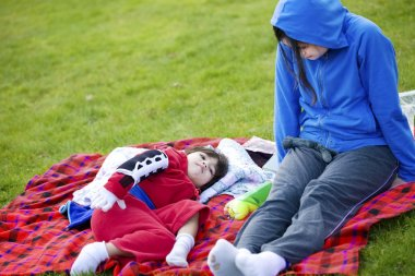 Teenager caring for disabled child at park