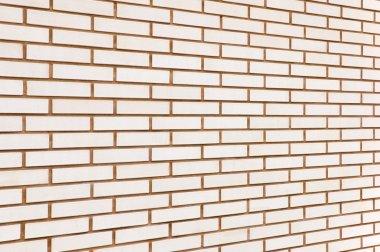 Beige colored fine brick wall texture background perspective, la
