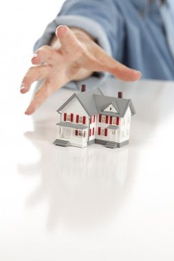 Womans Hand Reaching for Model House on White