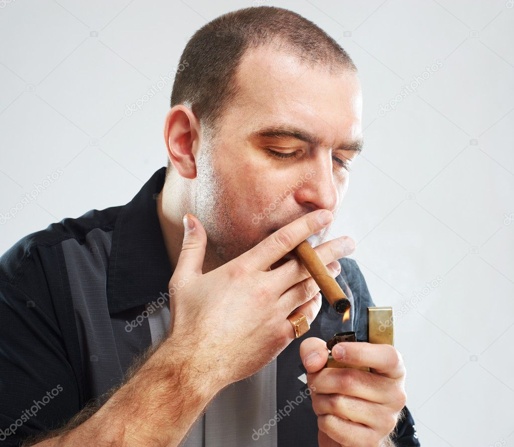 Portrait of serious smoking tough guy with cigar